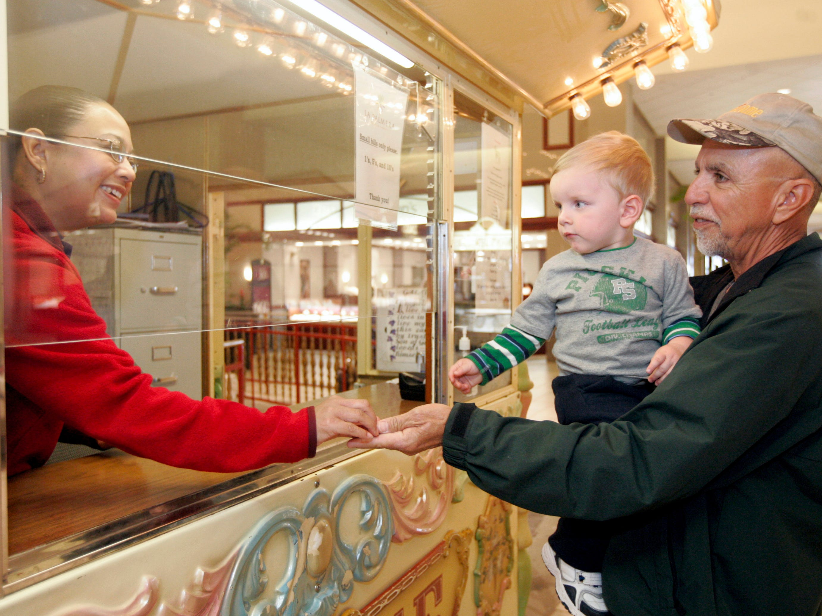 Carousel operator Yvonne Guerero (left) hands Joe Rodriguez of Corpus Christi his change as he and his grandson, 20-month-old Michael Ryan Rodriguez, get ready to ride Wednesday, Jan. 14, 2008 at La Palmera mall in Corpus Christi. Joe Rodriguez said it was his grandson's fourth time to ride that morning.