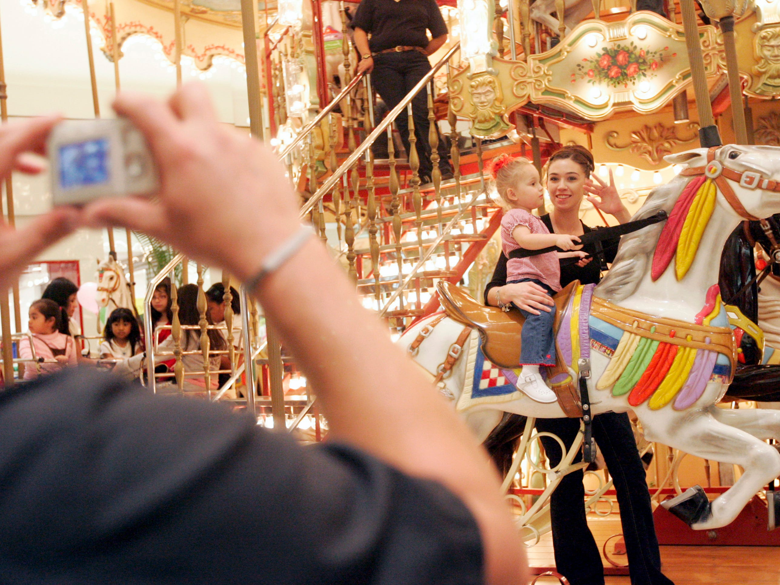 Stefanie Simmons waves to husband, Travis, as she and 2-year-old Kadie Simmons start spinning on the carousel Saturday, Jan. 31, 2009 at La Palmera in Corpus Christi. Stefanie Simmons said the carousel was always a special treat for their daughter each time they came to the mall.