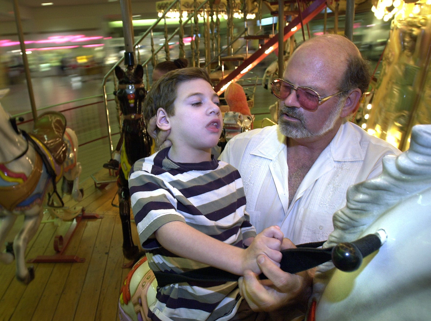 John Madden helps his son John Terry ride the carousel at the Padre Staples Mall in June 2000. Although John Terry has many disabilities, Madden wants him to experience as much as he can.
