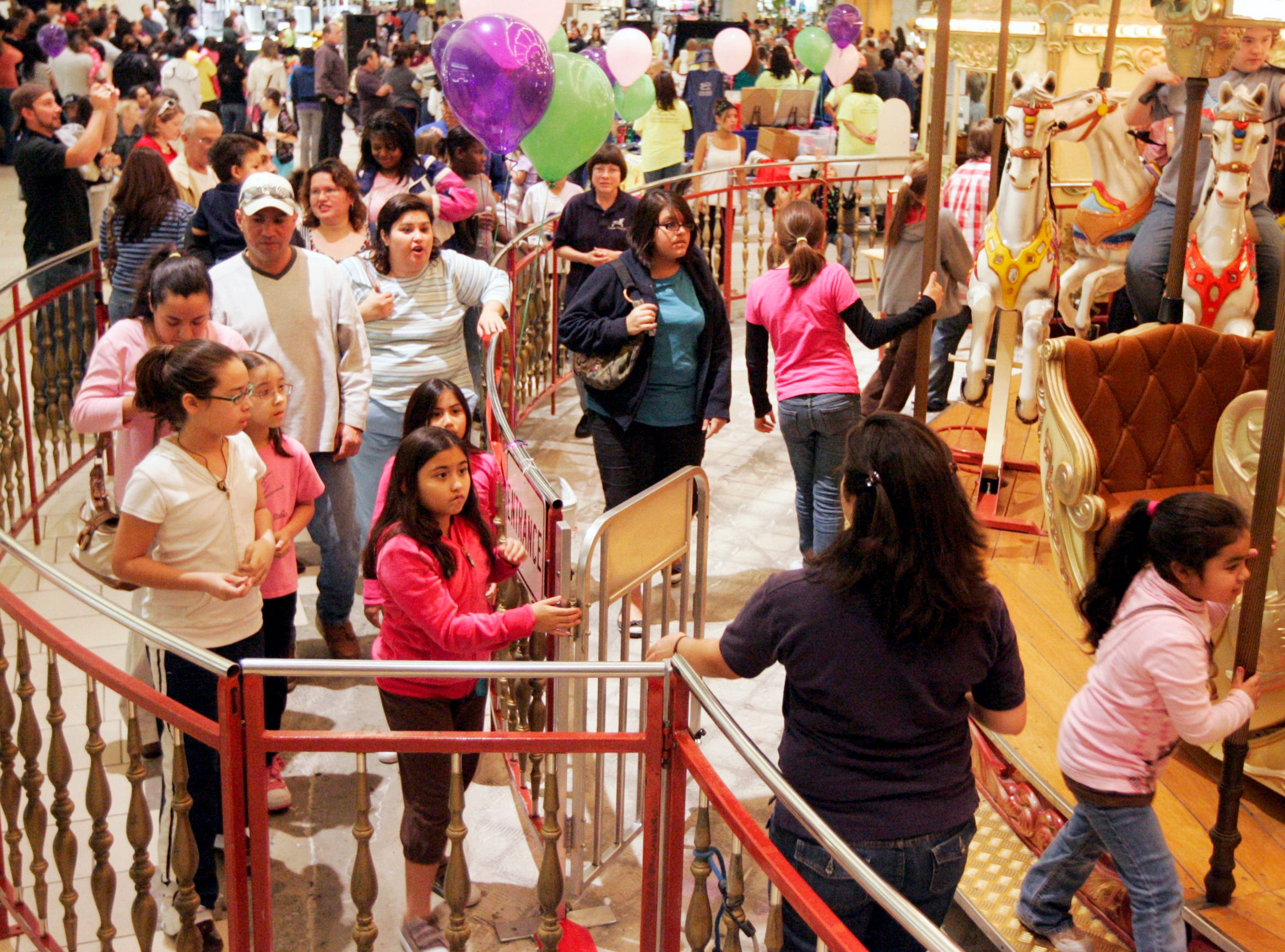 Carousel manager Irene Saldana takes tickets as a line of people wait to take a ride Saturday, Jan. 31, 2009 at La Palmera in Corpus Christi. The last day of carousel operation plus a separate event in the mall courtyard brought a steady flow of shoppers to the attraction.