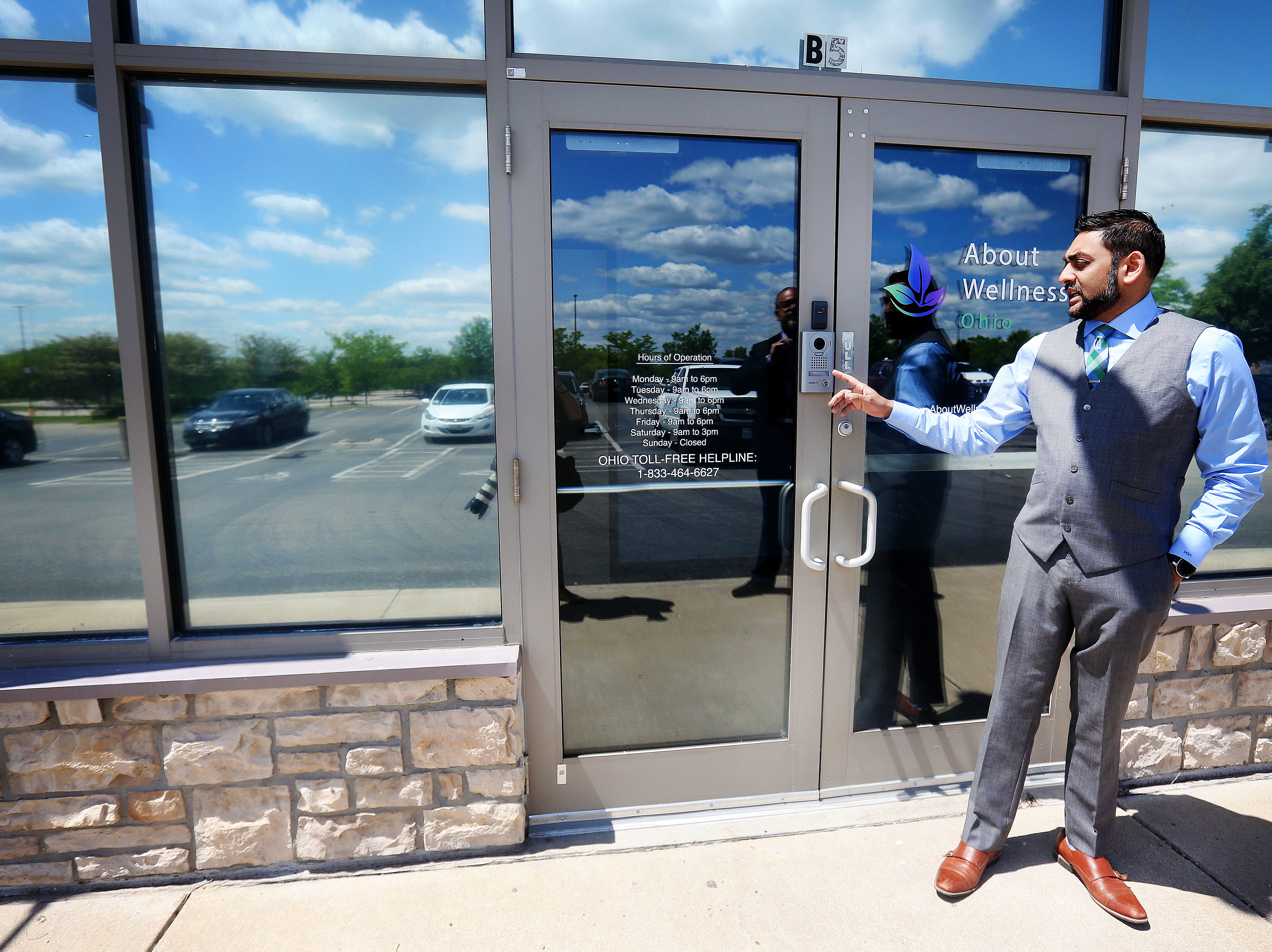 Mac Amin, dispensary manager at About Wellness Ohio, points out the camera on the door of the Lebanon facility. People must identify that they have a registered medical marijuana card before they are allowed to enter inside the building.