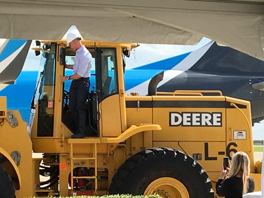 Amazon founder Jeff Bezos climbs into a front loader May 14, 2019, at Cincinnati/Northern Kentucky International Airport to break ground on a $1.5 billion Prime Air hub.