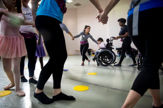 Ellen Wisner holds Evelyn Ortiz's hand as Erin Butler pushes her wheelchair to dance in a circle at the Ballet Moves class at the Cincinnati Ballet Saturday, February 2, 2019.