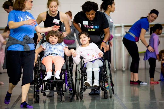 Kameron Walker and Evelyn Ortiz hold hands during the partner dances, as Bailey DeCoursey and Erin Butler push their wheelchairs across the studio at the Cincinnati Ballet Saturday, February 2, 2019. Each dancer is paired with an experienced physical therapist from Cincinnati Children's Hospital.