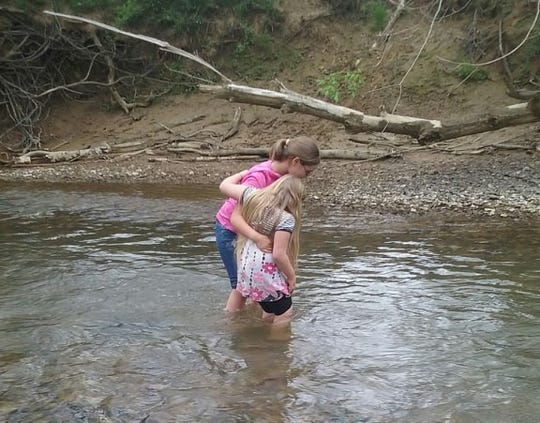 Penny Beckwith-Carter's youngest daughters, Morgan and Alyssa, play in a creek near their home in Piketon, Ohio.
