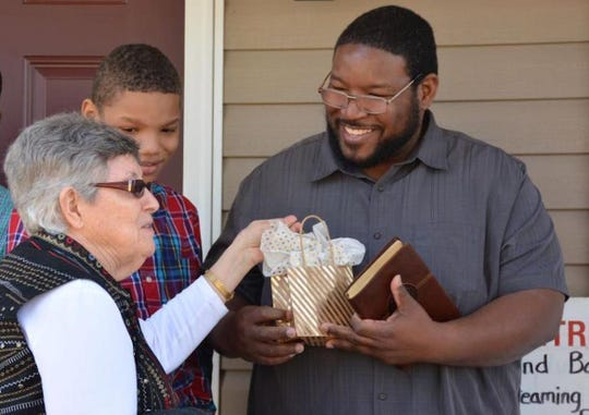 Homeowner Messiah Sadler accepts a gift at the dedication of his new Habitat home in March