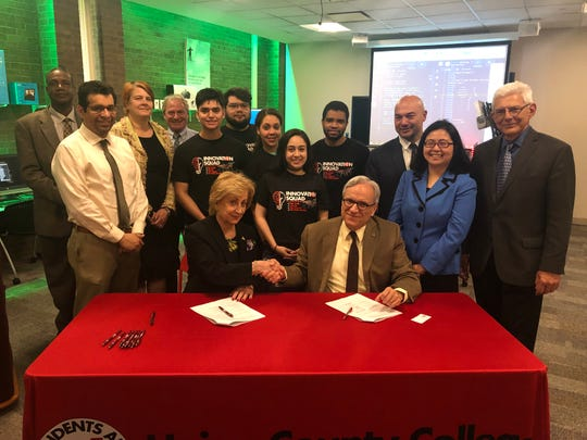 At the table are Union's Vice President for Academic Affairs Dr. Maris Lown and NJIT's Provost and Senior Executive Vice President Dr. Fadi P. Deek. Standing from left are NJIT's Vice Provost for Undergraduate Studies Laurent Simon, Union's Dean of Social Sciences/Business/History Dr. Carlos Barrezueta, Union's Dean of STEM Dr. Liesl Jones, Union's Director of Instructional Design Dr. Jeffrey Gutkin, Union students, Union's Assistant Vice President for Academic Affairs and Dean of the Scotch Plains Campus Dr. Bernard Polnariev, NJIT's Associate Provost for Enrollment Management and Academic Services Wendy Lin-Cook, and NJIT's Senior Vice Provost for Academic Affairs and Student Services Basil Baltzis.