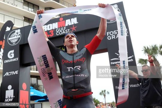 TJ Tollakson celebrates after winning the during IRONMAN 70.3 Gulf Coast on May 11, 2019 in Panama City, Florida.