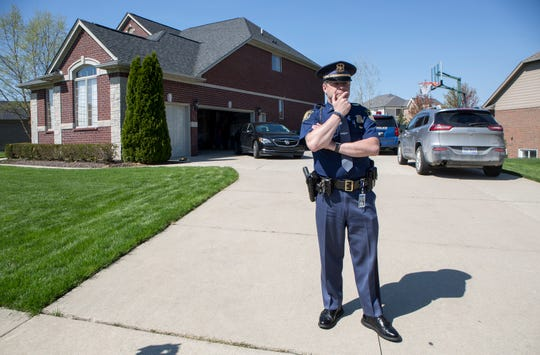 Michigan State Police public information officer F/Lt. Michael Shaw stands outside the home of Macomb County Prosecutor Eric Smith as the home is raided in Macomb Twp., Mich., Monday, May 13, 2019.