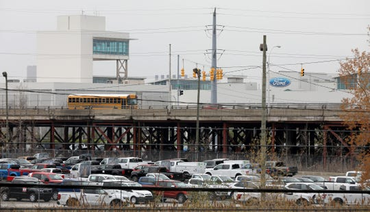 A school bus and other vehicles cross over the Miller Road Bridge in Dearborn with part of the Ford Motor Company Dearborn Truck Plant in the background on Thursday, April 2, 2019.