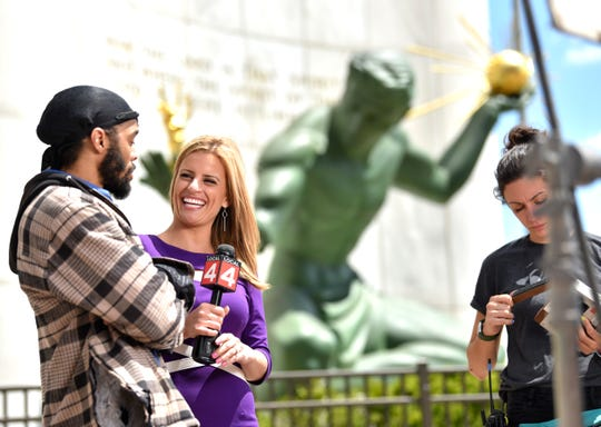 Local 4 reporter Kim DeGiulio, right, interviews Robert Shannon, of Detroit, in front of the Spirit of Detroit, during a break in the filming of a Big Sean music video.