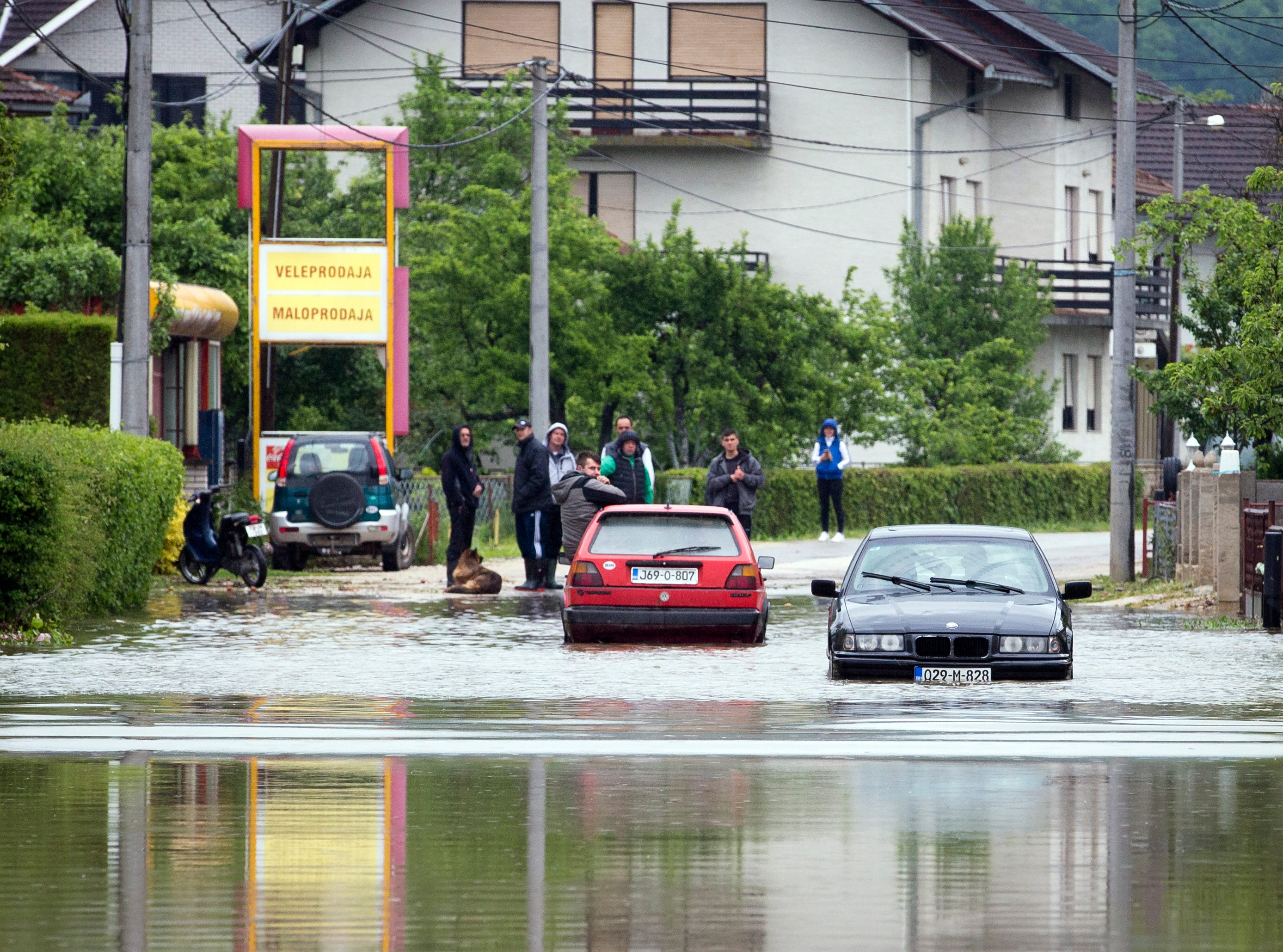 Residents attempt to drive through a flooded street in Sanski Most, Bosnia-Herzegovina, Tuesday, May 14, 2019. Homes and roads have been flooded in parts of Bosnia after rivers broke their banks following heavy rains, triggering concerns Tuesday of a repeat of floods five years ago when dozens died.