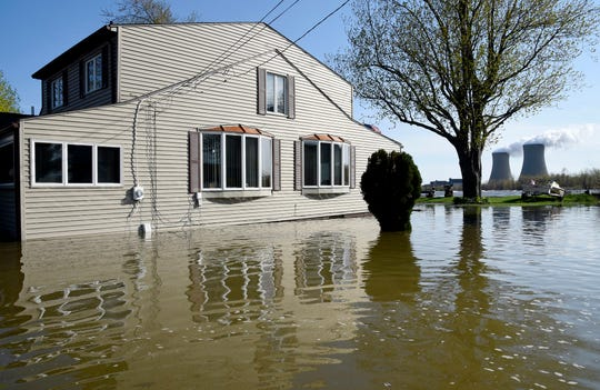 In this May 8, 2019 photo, a home surrounded by water on Lakeshore Dr. in the south end of Estral Beach in Berlin Township Mich., sits near the Fermi 2 in the background.