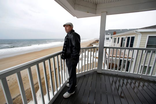 Real estate agent Tom Saab stands on a oceanfront deck at a condo he developed in Salisbury, Mass.