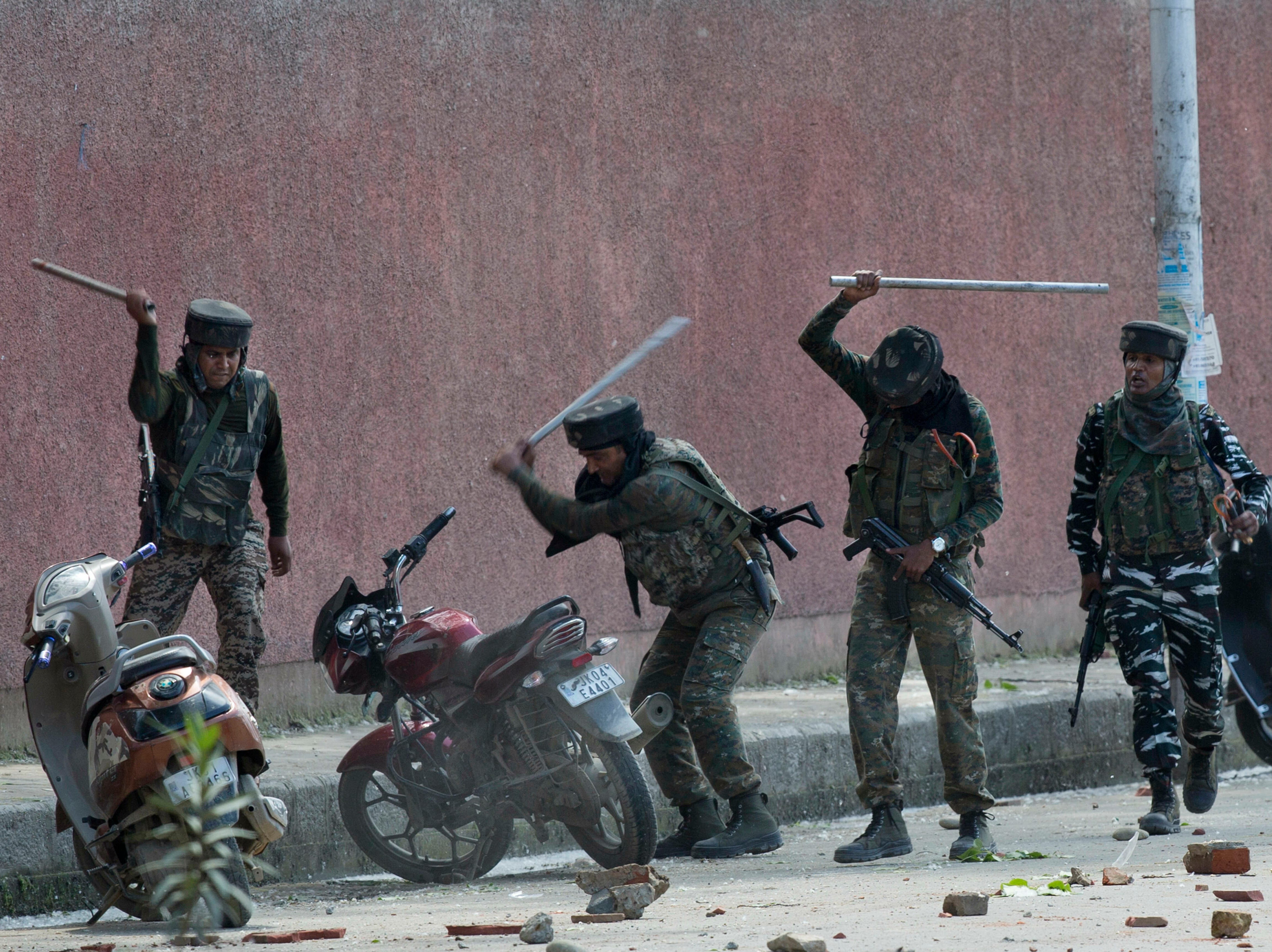Indian paramilitary soldiers break two wheelers parked outside a college as they clash with students protesting against the alleged rape of a 3-year-old girl in Srinagar, Indian controlled Kashmir, Tuesday, May 14, 2019. Protests continued for the third day Tuesday even as government forces fired shotgun pellets and tear gas to stop stone-throwing protesters from marching.