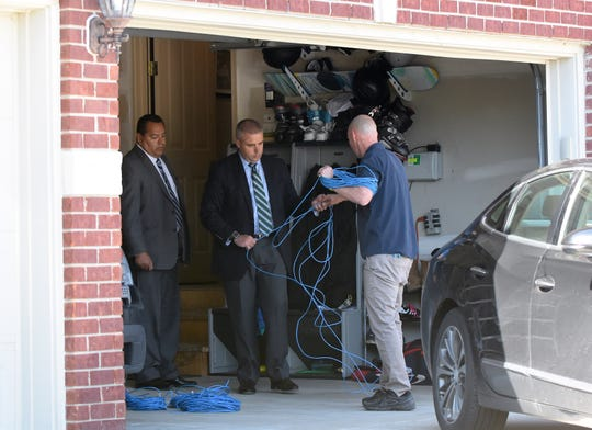Michigan State Police officers search the garage of Macomb County Prosecutor Eric Smith's Macomb Township home on Tuesday.
