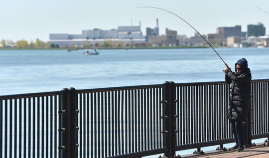 Jenny Zhang, of Canton Twp., fishes the Detroit River from John Dingell Park in Ecorse.  A  $1.9 million grant from the Ralph C. Wilson, Jr. Foundation will help complete plans for 3.5 miles of trail gaps and enhance the Iron Bell Trail connections between Detroit and Downriver communities.