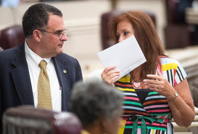 Rep. Terri Collins, right, chats with Rep. Chris Pringle on the house floor at the Alabama Statehouse in Montgomery, Ala., on Tuesday May 14, 2019.  Collins, who had exemptions for rape in bills introduced in past sessions, said lawmakers could come back and add exceptions if states regain control of abortion access.