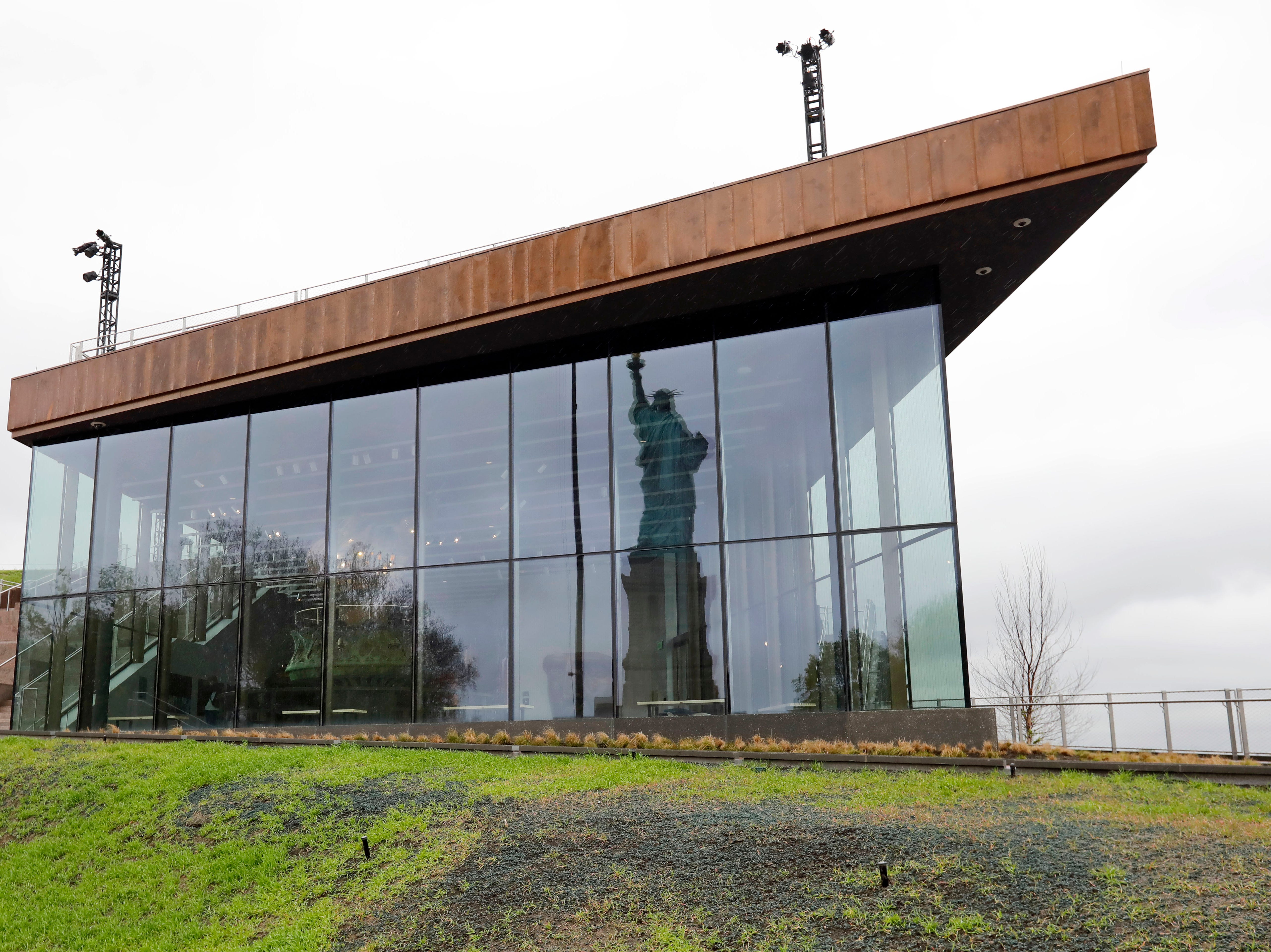 The Statue of Liberty is reflected in the windows of the new Statue of Liberty Museum. The entire structure is meant to connect to Lady Liberty, using the same granite that's part of the statue pedestal and including copper as a nod to the material the statue is made of, said Cameron Ringness, the project designer at FXCollaborative, which created the museum's overall design.