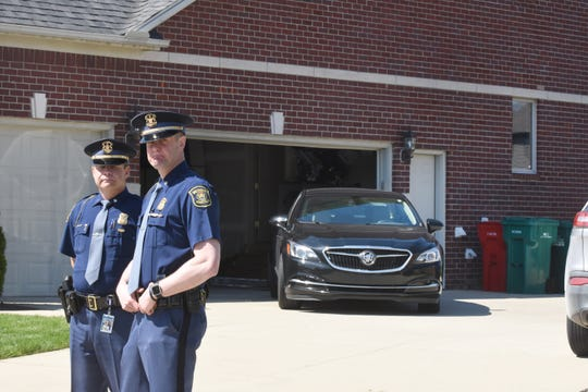 Michigan State Police Lt. Michael Shaw (left) and Lt. Darren Green stand outside the home of Macomb County prosecutor Eric Smith as they raided Smith's home on Tuesday, May 14, 2019.