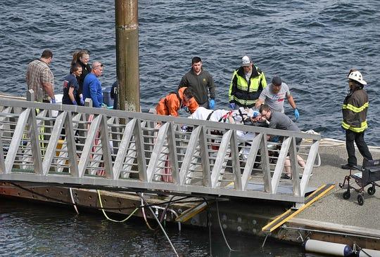 Emergency response crews transport an injured passenger to an ambulance at the George Inlet Lodge docks, Monday in Ketchikan, Alaska.