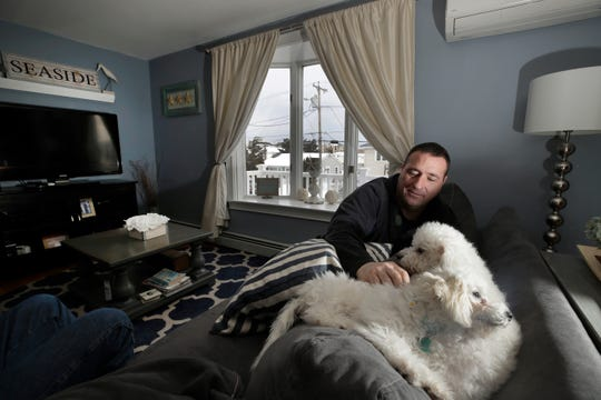 Denis Champagne, Jr. plays with his dogs Maebelle and Isabel at home near the coast in Salisbury, Mass.