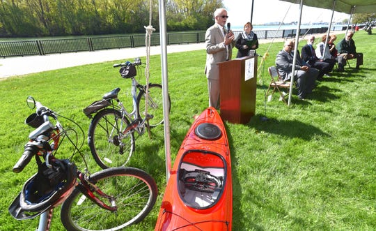 Wayne County Executive Warren Evans addresses attendees from the podium Tuesday at John Dingell Park in Ecorse.