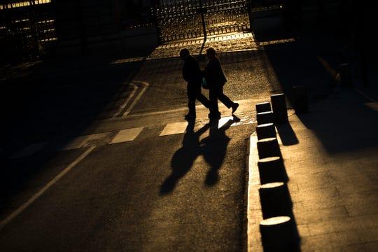 An elderly couple walks across a street near the Royal Palace in Madrid. I