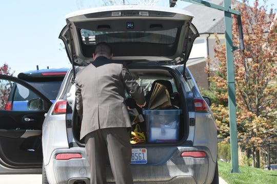 Michigan State Police investigators load gathered evidence at the home of Macomb County prosecutor Eric Smith.