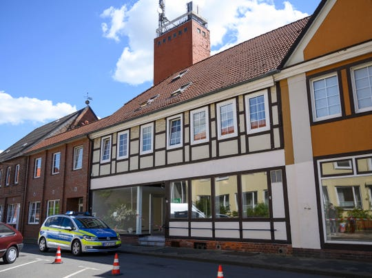 A police car stands in front of a building where the bodies of two women have been found at an apartment, in Wittlingen, northern Germany, Monday, May 13, 2019.