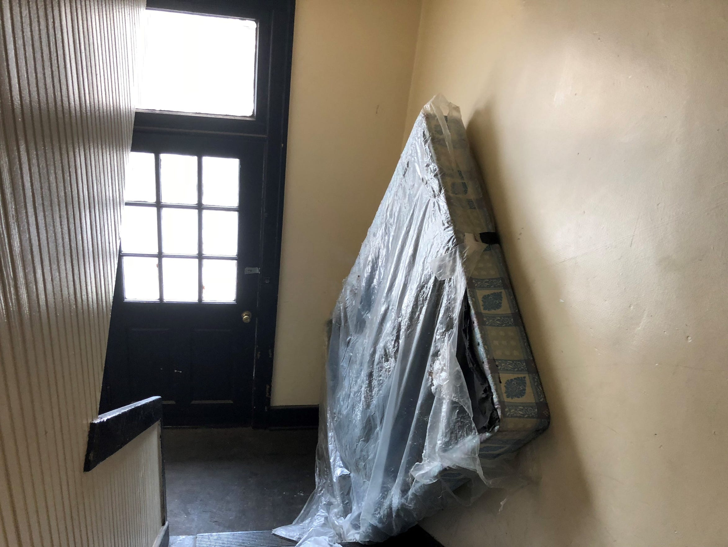 A used, broken mattress blocks the back stairway of Bretton Hall in August 2018, one of three Henry Street apartment buildings owned by an Ilitch-linked entity.