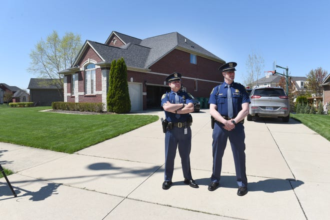 Michigan State Police Lt. Michael Shaw (left) and Lt. Darren Green stand outside the home of Macomb County prosecutor Eric Smith while their fellow officers raid Eric Smith's home on Tuesday, May 14, 2019.
