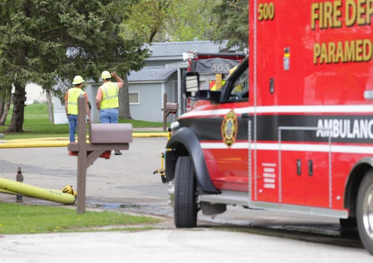 Alliant Energy workers look over the scene where a car hit a trailer Tuesday afternoon, causing a gas leak in the Gaslight Terrace Mobile Home park in North Fond du Lac. Residents within a half mile of the scene are being evacuated.