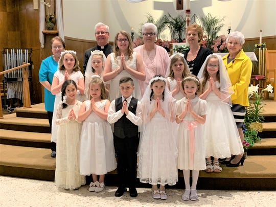 Second graders who celebrated their First Holy Communion at Immaculate Conception, Port Clinton, were in front: Mia MacBride, Micaela Wiechman, Dylan Reynolds, Kate Leneghan, and Suzannah Osborne. In the middle were Ella Lynd, Aleah Gonya, Ava Hutchinson, Leah Shawl ,Grace Wadsworth. In back are Sr. Marilyn Angel SND, Father John Missler,  Connie Snyder, Penny Boyd, and Karen Bivens.
