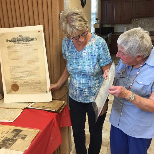 Linda Kohlman and Linda Dunn admire a few of the many documents on display for the 150th Anniversary celebration of St John's Evangelical Lutheran Church.