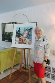"Cape Coral artist Cheryl Fausel and her painting, ""Reflections of Zurich II."" The watercolor work is part of the ""Art Lives Here"" exhibit, now being displayed on Lee County billboards."