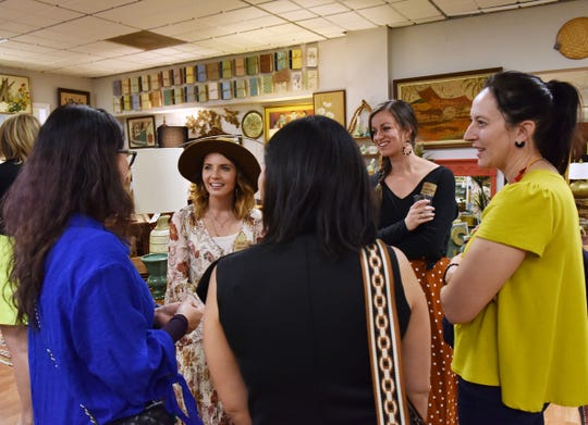 Eileen Beaver and Lindsay Jackman, middle, founders of GVL Creative Connections, talk with people during a recent meeting at Cottage Grove.