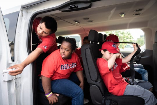 David Carlisle, 19, Tia Carlisle, 20, Skyler Carlisle, 7, wait in their family's 15-passenger-van with their siblings before their Mauldin Miracle League baseball game at Sunset Park, Saturday, May, 4, 2019.
