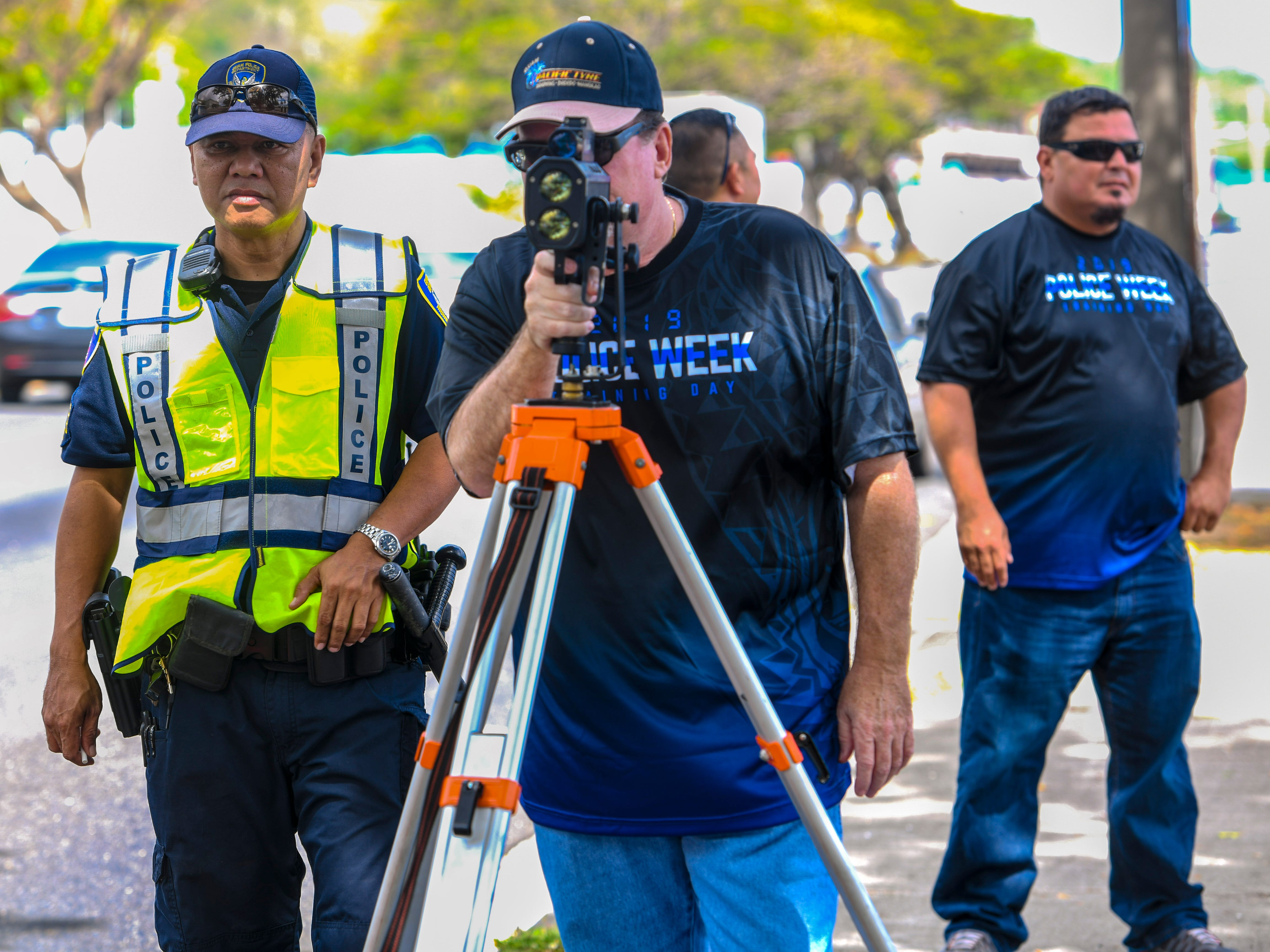 Don Perron, center, Pacific Tyre operations manager, tries his hand at operating a laser speed gun during a demonstration by the Guam Police Department's Highway Patrol Division in Anigua on Tuesday, May 14, 2019.