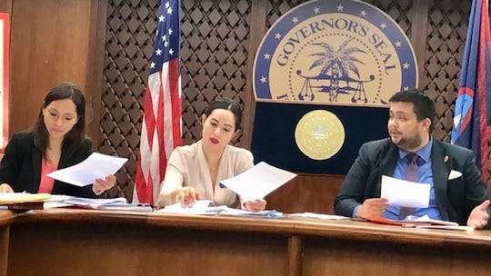 Guam Cannabis Control Board member William Parkinson, right, gestures as he talks about some of the questions from the public regarding the law on adult cannabis use, while Board Chairwoman Vanessa Williams, center, and Vice Chairwoman Dafne Shimizu, left, review documents during the board's second meeting on May 14, 2019.