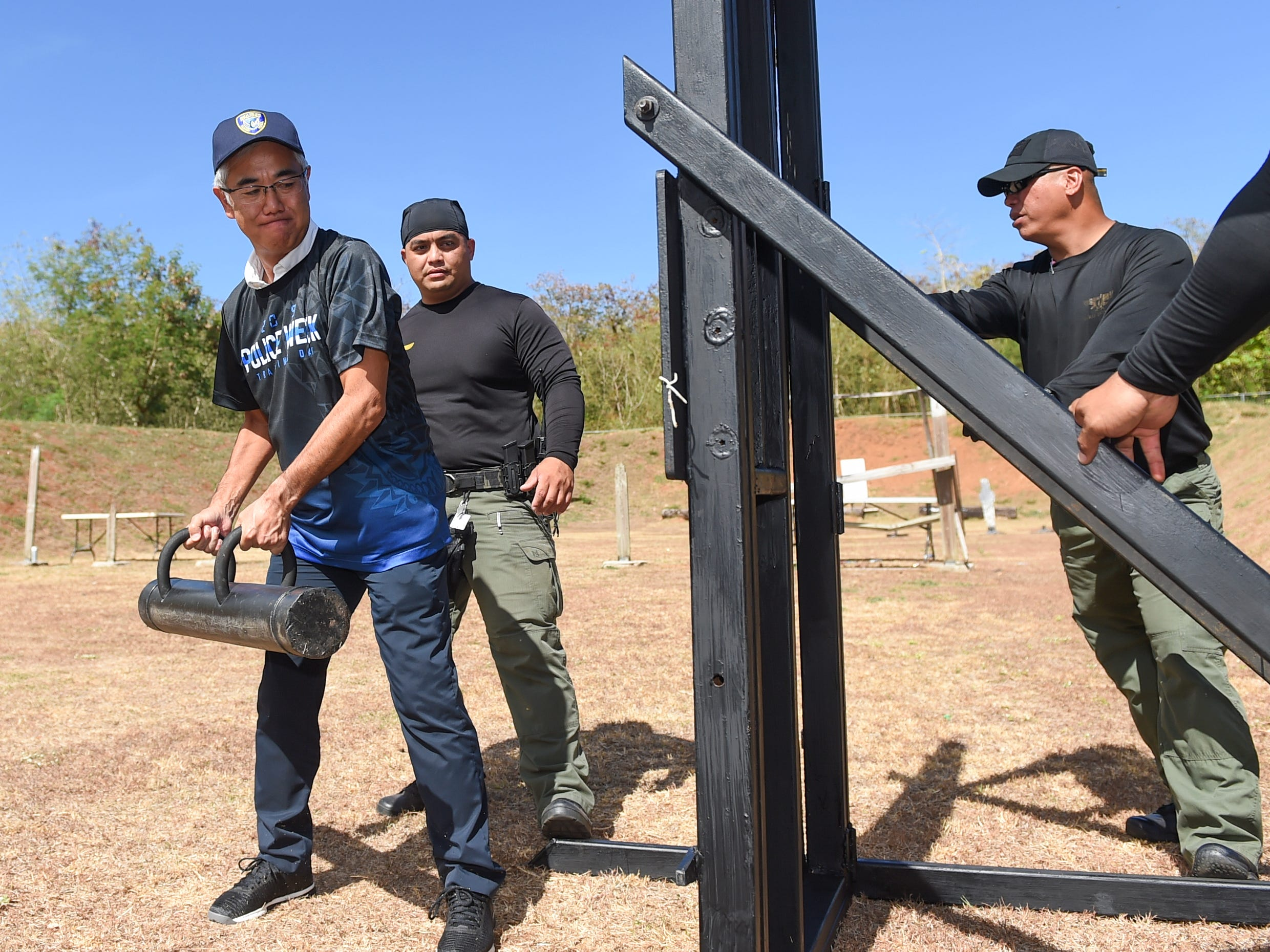 """Mitsuo """"Mike"""" Sato, P.H.R. Ken Micronesia, Inc. president, uses a battering ram while participating in a door breaching demonstration at the Guam Police Department's shooting range on the Guam Community College campus in Mangilao, May 14, 2019."""