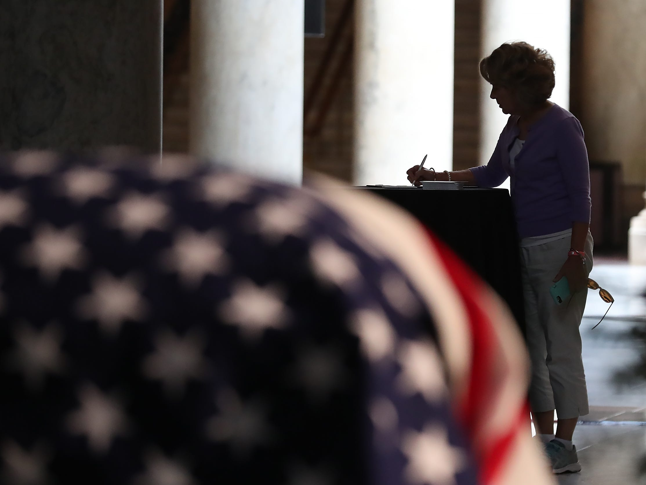 A woman signs a book as the public pays their respect to former Senator and Mayor Richard Lugar lying in state under the Statehouse rotunda, Tuesday, May 14, 2019.
