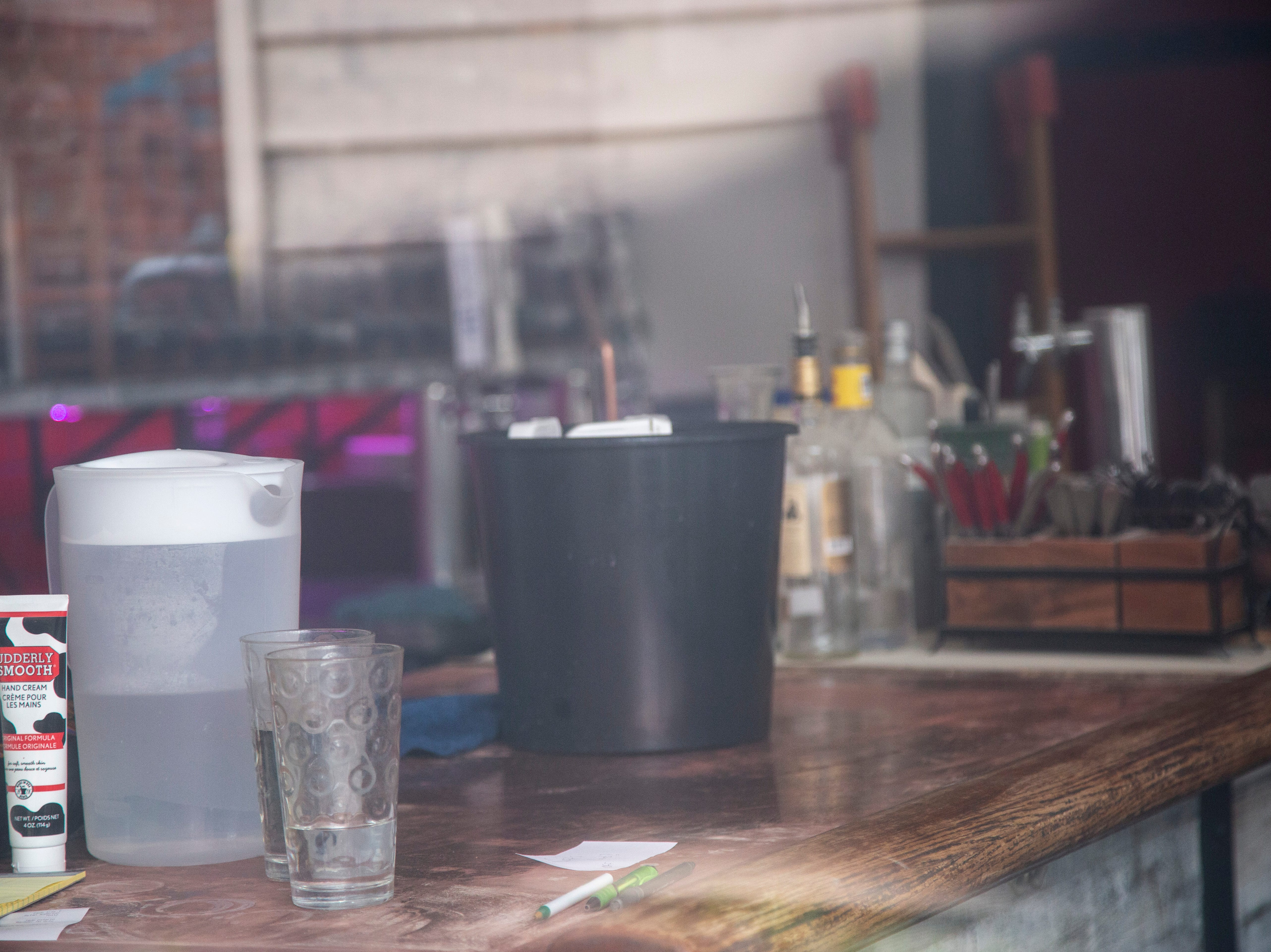 A half cleaned bar is surrounded by damage, Tuesday, May 14, 2019, at Linn Street Dive in Iowa City, Iowa.