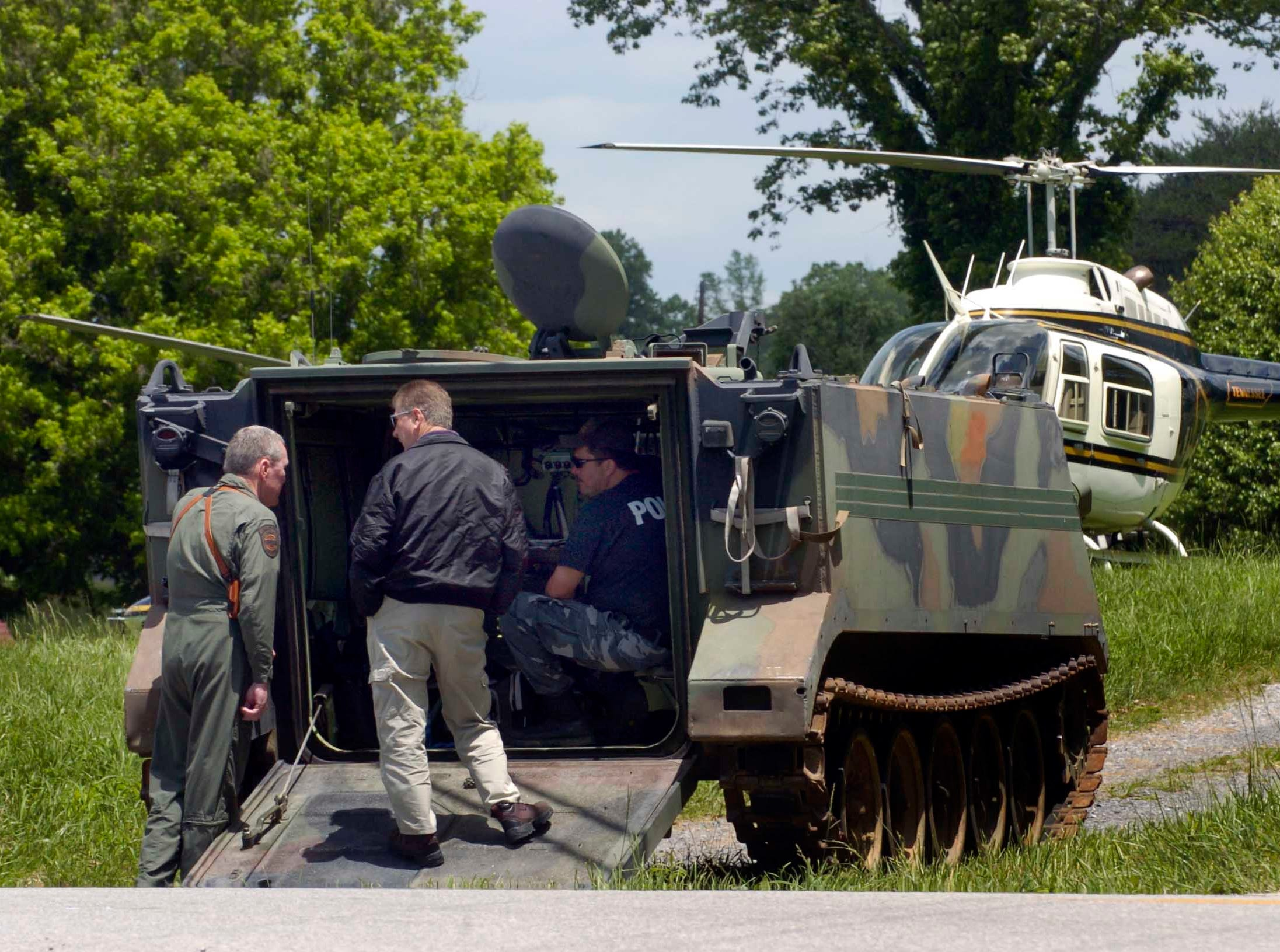 Officers prepare an armoured personnel carrier near the landing site for the Tennessee Highway Patrol helicopters across the street from Midway High School Friday afternoon. Officers continued to search the woods of South Roane County Friday looking for Leon Houston after he and his brother, Rocky, allegedly ambushed and killed Deputy Bill Jones, 53, and friend Mike Brown on the evening of Thursday, May 11.