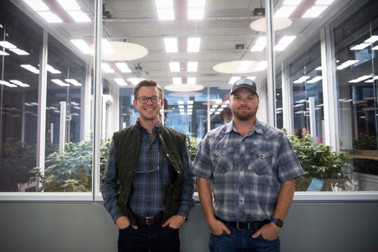 Founders, from left, Joe Fox, and Erich Maelzer, stand in front of a grow room at a soft opening of Blühen Botanical's wellness and CBD product retail center on 111 East Jackson Ave in downtown Knoxville Tuesday, May 14, 2019.