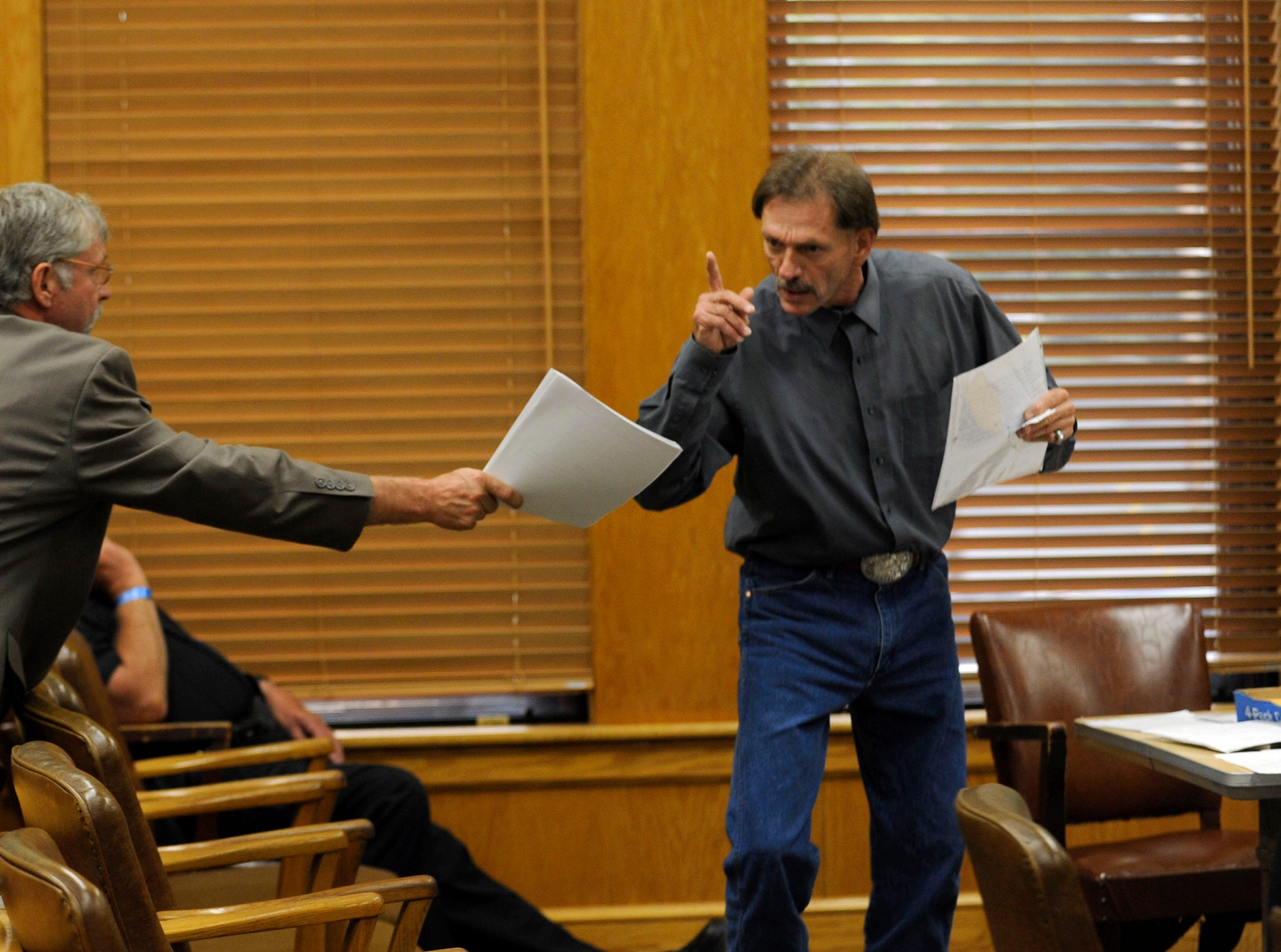 Clifford Leon Houston, right, stops mid-sentence to look at a note from his brother Rocky while arguing his case in Roane County Circuit Court Friday, Jul. 2, 2010. Leon Houston is accusing an ongoing conspiracy against him and his family. Senior Judge Walter Kurtz refused to recuse himself and reserved judgment on the lawsuit.