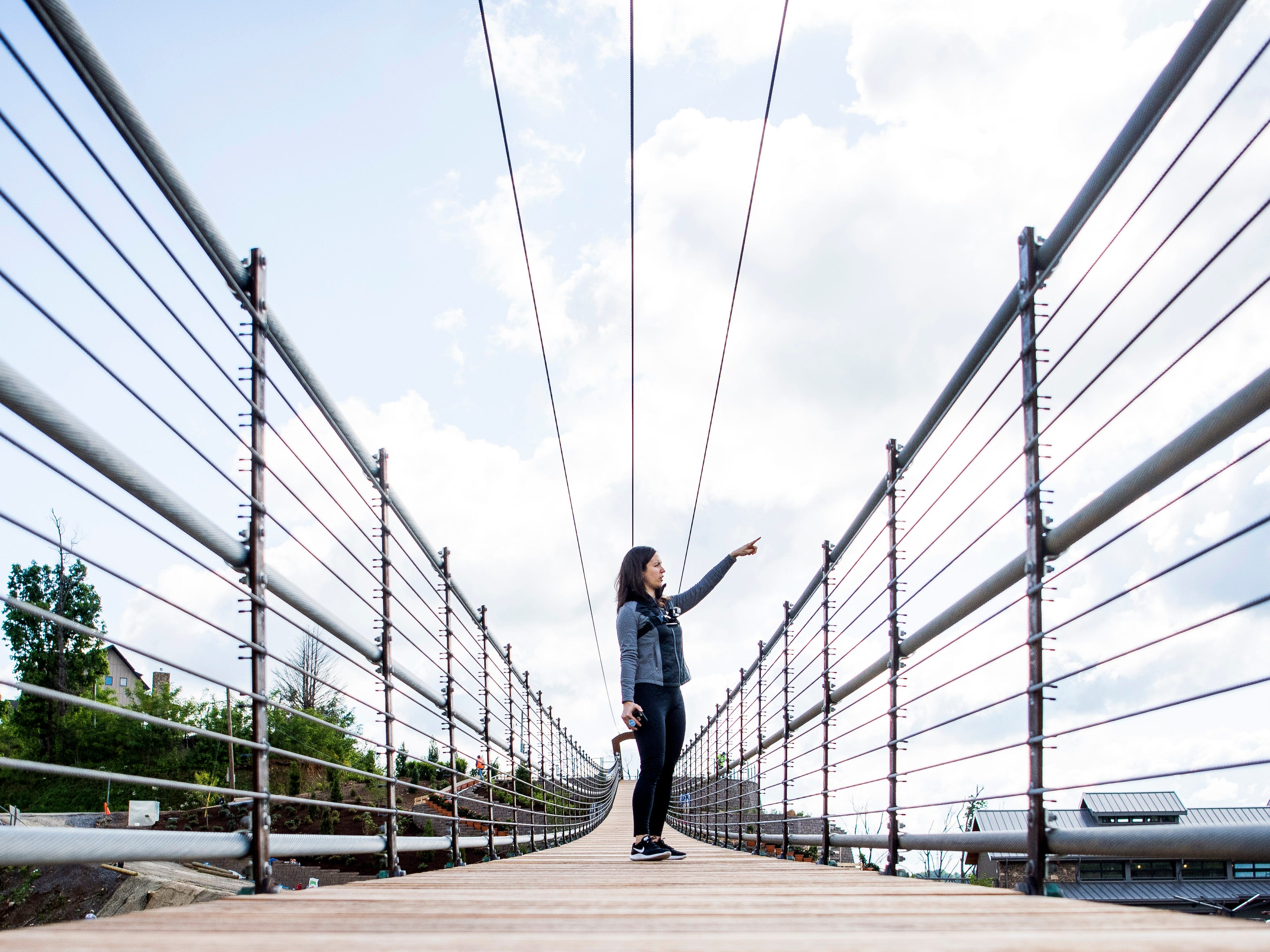 Knoxville News Sentinel reporter Brenna Mcdermott points out views of the Smoky Mountains from the Gatlinburg SkyBridge, North America's longest pedestrian suspension bridge, on Tuesday, May 14, 2019.
