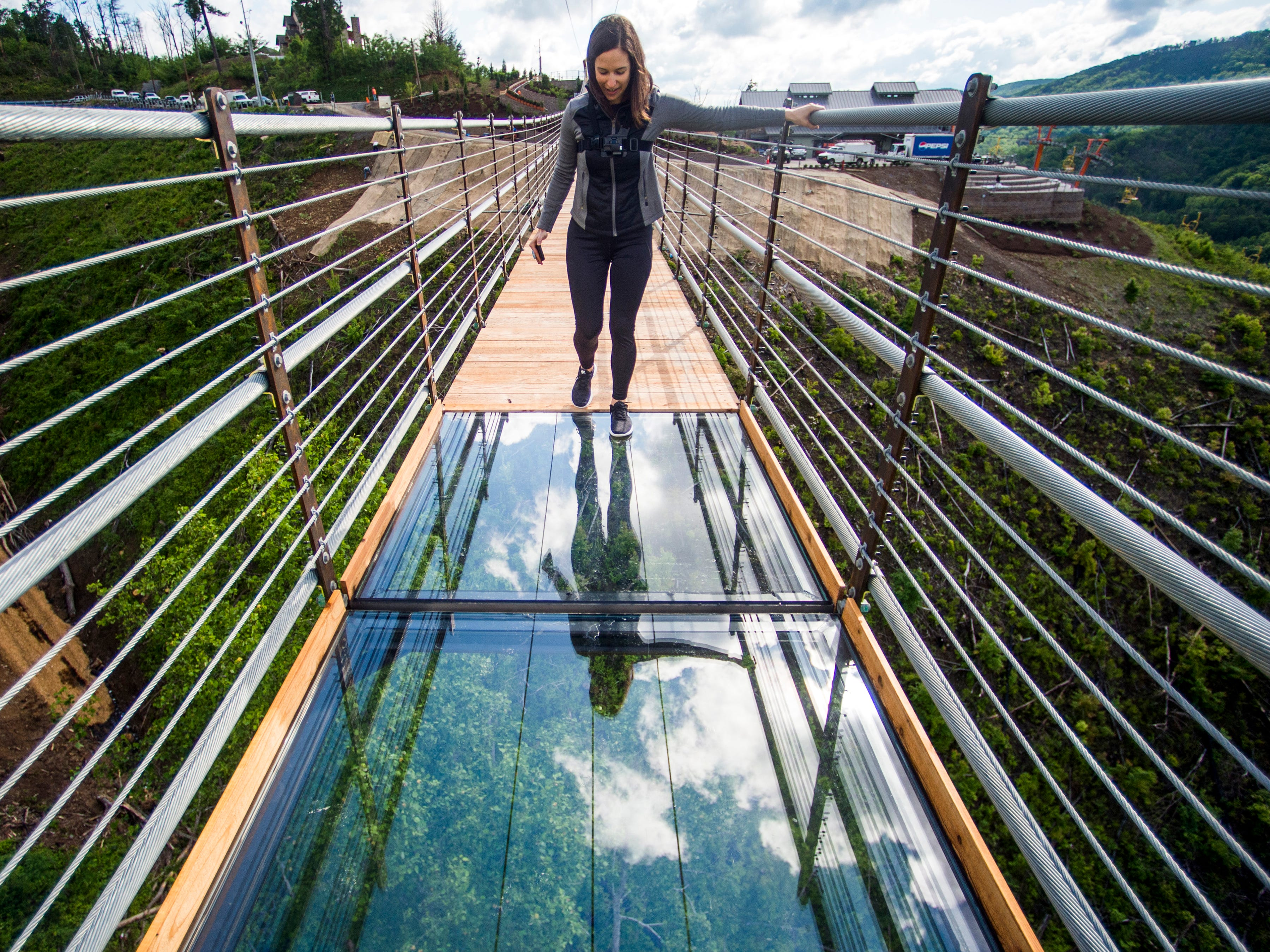 Knoxville News Sentinel reporter Brenna McDermott takes a step onto the glass-floor panels in the middle of the Gatlinburg SkyBridge, North America's longest pedestrian suspension bridge, on Tuesday, May 14, 2019.