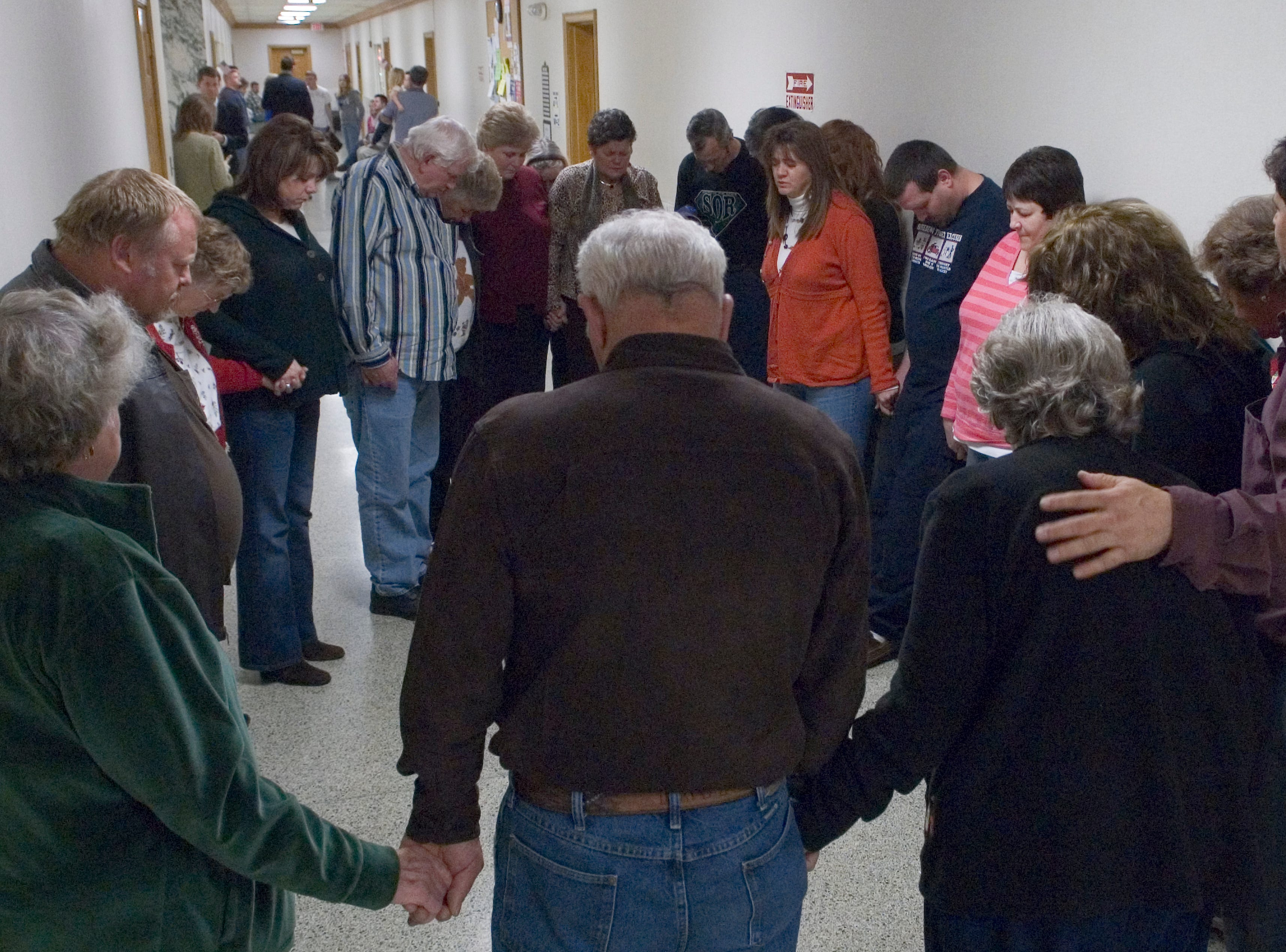 Lisa Burris, center, leads family and friends in a prayer Thursday for her brother Rocky Joe Houston as they wait outside the courtroom for a verdict in his double first-degree murder trial. Thursday, December 18, 2008