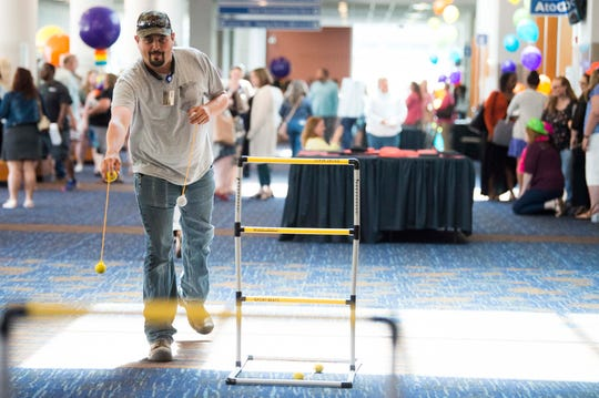 Jeremy Ross of Washburn, Tenn. plays a yard game during a Helen Ross McNabb Center employee awards celebration at the Knoxville Convention Center, Tuesday, May 14, 2019.